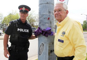 Sarnia Police Const. Chris Moxley and Art Speed with the Lambton Drug Awareness Action Committee tie a purple ribbon at the Exmouth Street at Indian Road intersection in Sarnia Tuesday. The committee's annual Purple Ribbon Campaign to create awareness about alcohol-related crashes runs until May 31. Tyler Kula/Sarnia Observer/Postmedia Network