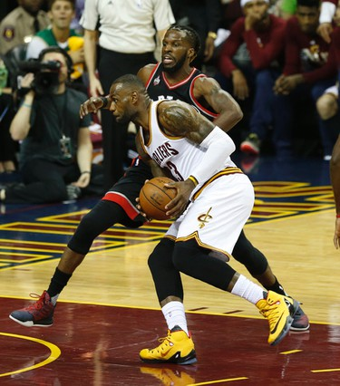 Cleveland Cavaliers LeBron James (23) is guarded by Toronto Raptors DeMarre Carroll (5) in Cleveland on Tuesday May 17, 2016. Jack Boland/Toronto Sun/Postmedia Network