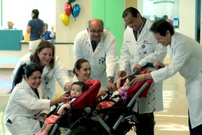 In this photo provided by Driscoll Children's Hospital, from left, Driscoll Children's Hospital physicians Angelina Bhandari, Jane Lyon, Vanessa Dimas, Karl Maher, Omar Cruz-Diaz, and Miguel DeLeon, say goodbye to former conjoined twins Scarlett and Ximena Hernandez-Torres, who left Driscoll Children's Hospital in Corpus Christi on Wednesday morning, May 18, 2016, five weeks after their separation surgery. (Driscoll Children's Hospital via AP)