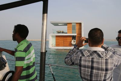 In this Monday, May 9, 2016 photo, a client takes snaps of a full-scale mock-up of the Floating Seahorse home on the waters of The Dubai World. The Seahorses, part of an ambitious larger hotel development called The Heart of Europe, seeks to attract something that sounds even more grandiose. That's saving The World, as the long-stalled Earth-shaped island project off Dubai's coast is called. (AP Photo/Kamran Jebreili)