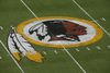 In this Aug. 7, 2014 file photo, the Washington Redskins logo is seen on the field before an NFL football preseason game against the New England Patriots in Landover, Md. (AP Photo/Alex Brandon)
