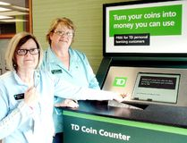Sharon Grainger, front, and Francine Waekens check out a new coin changer that was installed at the TD Canada Trust branch on St. Clair Street in Chatham, Ont., on Tuesday, April 2, 2013. (BOB BOUGHNER/THE CHATHAM DAILY NEWS/Postmedia Network)