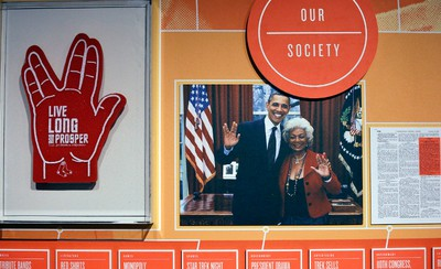 """In this photo taken Wednesday, May 18, 2016, a foam finger in the shape of the Vulcan salute is displayed along with a photo of President Barack Obama and actress Nichelle Nichols, who played Lt. Nyota Uhura in """"Star Trek,"""" in a display for the exhibit, """"Star Trek: Exploring New Worlds"""" for a 50th anniversary celebration of the franchise at the EMP Museum, in Seattle. The exhibit opens on Saturday.  (AP Photo/Elaine Thompson)"""