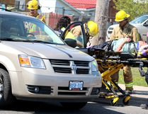 Paramedics and firefighters help a man hurt in a two-vehicle crash at a west-end intersection on Saturday.