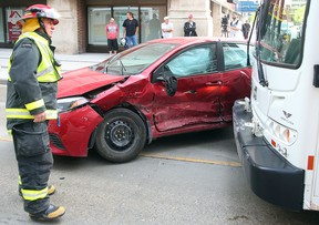 A Winnipeg firefighter examines damage following a collision between a car and a transit bus at Graham and Hargrave in Winnipeg, Man. Sunday, May 22, 2016. (Brian Donogh/Winnipeg Sun/Postmedia Network)