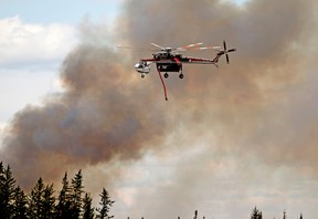 A helicopter battles a wildfire south of Fort McMurray, Alberta on May 8, 2016.
