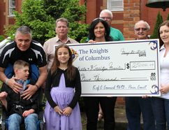 The Pain Court Knights of Columbus delivered two donations of $12,500 to families that have a child with serious medical needs during a cheque presentation in Pain Court, Ont. on Saturday May 21, 2016. Pictured from front left, are: John Bechra hold his step-daughter Lainey Goodreau, 5, who has Galloway-Mowat Syndrome, Enzo Coletta with his son Dante, 13, who has Christianson Syndrome, Lainey's sister Lily Labonte, 8, Wanda Coletta and Kate Kreitzer. From back left are Pain Court K of C members Norb King, Bob Bechard and Bob Demers. Ellwood Shreve/Chatham Daily News/Postmedia Network