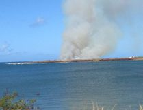 In this photo provided by Ryan Richardson, plumes of smoke are seen from Port Allen Harbor across an inlet after a plane crashes just outside Port Allen Airport on the island of Kauai, on Monday, May 23, 2016. Multiple people died after a skydiving tour plane crashed and caught fire in Hawaii, one of two plane crashes reported Monday in the islands. (Ryan Richardson via AP)