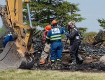 An investigator with the Ontario Fire Marshal's office and members of the Dutton-Dunwich Fire Department sift through the charred remains of a home at 31222 Edinborough Line, where a 37-year-old woman was found dead, near Dutton, Ont. on Sunday (Craig Glover/The London Free Press/Postmedia Network)