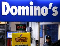 A worker carries a pizza for delivery as he exits a Domino's pizza store in Sydney, Australia, in this August 12, 2015 file photo. Domino's is expected to announce Q3 earnings on October 8, 2015. REUTERS/David Gray/Files