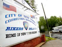 In this May 7, 2011 file photo, a New York City Department of Corrections bus passes the sign to the Rikers Island jail complex in New York. (AP Photo/Seth Wenig, File)