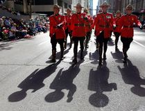 """Members of the RCMP march during the Calgary Stampede parade in Calgary, Friday, July 5, 2013. Mounties wearing tiny video cameras must hit the record button when there is """"a high likelihood"""" they'll use force against someone, says an interim RCMP policy on use of the devices.In general, officers have discretion as to when to turn on the body-worn cameras that clip on a uniform, or may be embedded in glasses or a helmet. THE CANADIAN PRESS/Jeff McIntosh"""