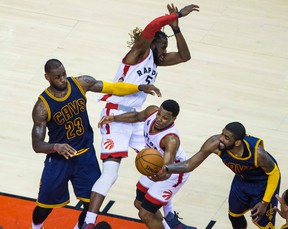 Raptors' Kyle Lowry (bottom) with DeMarre Carroll (top) and Cavaliers LeBron James (left) and Kyrie Irving (right) battle for the ball during fourth quarter action in Game 4 of the Eastern Conference final in Toronto on Monday, May 23, 2016. (Ernest Doroszuk/Toronto Sun)