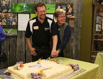 """Myrna Pearman, right, and Doug Anderson, President of Peavy Industries Ltd. cut the cake during the celebration of the success of Pearman's book, """"Backyard Bird Feeding: An Alberta Guide"""" during opening day at Ellis Bird Farm on Monday, May 23. (Ashli Barrett, Lacombe Globe)"""