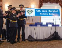 Representatives of the OPP, left, with the brothers of Const. Craig Campbell unveil the Ministry of Transportation sign that will go on either end of the Kincardine bridge on Highway 21 in honour of his sacrifice 30 years ago. (Darryl Coote/Reporter)