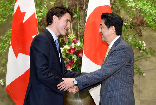 Prime Minister Justin Trudeau (L) is welcomed by his Japanese counterpart Shinzo Abe upon his arrival at Abe's official residence in Tokyo, Japan, May 24, 2016. REUTERS/Toru Yamanaka/Pool