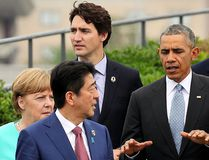 Japanese Prime Minister Shinzo Abe, centre, chats with U.S. President Barack Obama, fifth left, as other leaders of Group of Seven industrial nations, from left, Italian Prime Minister Matteo Renzi, German Chancellor Angela Merkel, Abe, Canadian Prime Minister Justin Trudeau, top, Obama, British Prime Minister David Cameron and European Council President Donald Tusk, walk along after a family photo session on the first day of the G7 summit meetings in Shima, Japan, Thursday, May 26, 2016. (Japan Pool via AP)