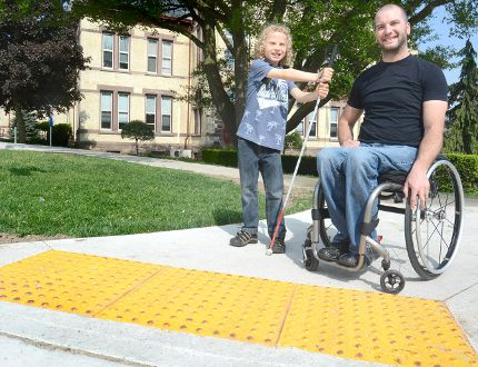 Jonah Manley and Roger Koert are shown with one of the new Tactile Walking Surface Indicators that are being installed on curb cuts in the city. SCOTT WISHART/The Beacon Herald