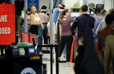Passengers pass through airport security at LaGuardia Airport in New York, Thursday, May 26, 2016. The Transportation Security Administration will add 768 new screeners by mid-June to deal with increasingly long airport security lines that have caused passengers to miss flights even before the busy summer travel season, the agency's chief told Congress on Wednesday. Most of the new screeners will be sent to the nation's busiest airports in Chicago, New York, Atlanta, Los Angeles and other hubs. (AP Photo/Seth Wenig)