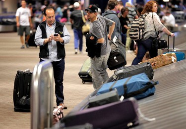 Passengers retrieve their luggage after their flights, Friday, May 27, 2016 at Sky Harbor International Airport in Phoenix. Travelers taking to the skies for the Memorial Day weekend said security lines are moving faster than expected after weeks of costly delays at U.S. airports. (AP Photo/Matt York)