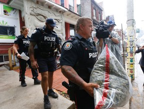 Police officers carry out pot and other items at Cannawide, a pot dispensary in Kensington Market in Toronto during a raid on the store on Thursday May 26, 2016. (MICHAEL PEAKE, Toronto Sun)