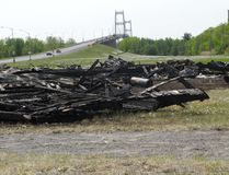 <p>The south span of the Seaway International Bridge is shown behind the scorched remains of the former Mohawks' protest shacks which caught fire Tuesday night at the Four Corners of Cornwall Island on Thursday May 26, 2016 in Akwesasne, Ont. Greg Peerenboom/Cornwall Standard-Freeholder/Postmedia Network