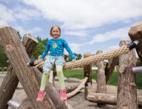 """KAYLA ISOMURA HIGH RIVER TIMES/POSTMEDIA NETWORK. Ellie Scheller, 6, sits on top of the """"log jam,"""" one of the new playground structures at Birchwood Park on May 24."""