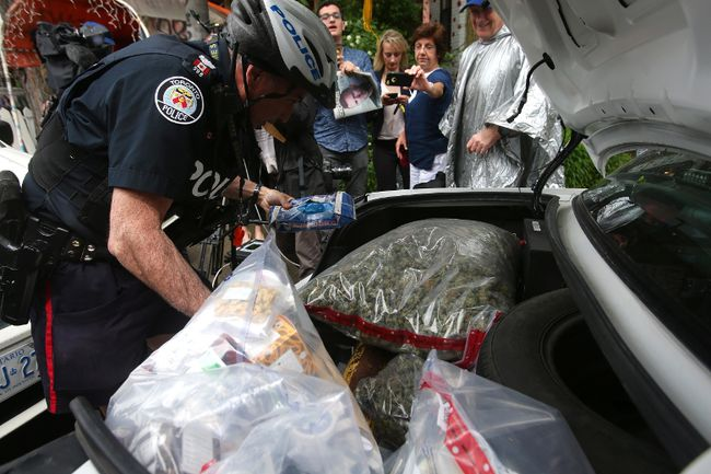 An officer involved in Thursday's dispensary raids loads up the trunk of a police cruiser with confiscated marijuana and other products. (THE CANADIAN PRESS)