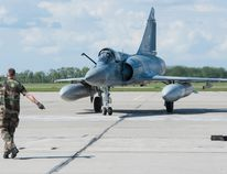 A member of the French Armed Forces directs a Mirage 2000-5 aircraft as it taxis on the runway at 4 Wing Cold Lake, Alberta for Exercise MAPLE FLAG on May 26, 2016. Photo: Cpl Manuela Berger, 4 Wing Imaging CK01-2016-0499-006