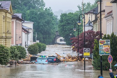 Cars are swept away on a flooded street in Simbach am Inn, southern Germany on June 1, 2016. Incessant rain in regions of Germany, France and Austria led to flash flooding Wednesday, forcing residents to seek refuge on rooftops and stranding hundreds of pupils at their school overnight, authorities said. / AFP PHOTO / dpa / Daniel Scharinger / Germany OUT