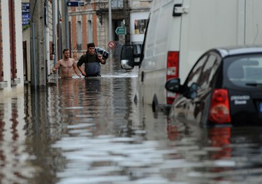 Two men walk in a flooded street as the city is flooded due to heavy rainfalls at Montargis, central France, on June 01, 2016. Torrential downpours have lashed parts of northern Europe in recent days, leaving four dead in Germany, breaching the banks of the Seine in Paris and flooding rural roads and villages.  / AFP PHOTO / GUILLAUME SOUVANT