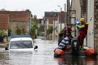 Rescuers evacuate residents onto a dinghy through a flooded street on June 1, 2016 in Souppes-sur-Loing, southeast of Paris. Torrential downpours have lashed parts of northern Europe in recent days, leaving four dead in Germany, breaching the banks of the Seine in Paris and flooding rural roads and villages.   AFP PHOTO / KENZO TRIBOUILLARD
