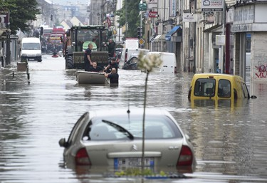Rescuers stand in a boat during a rescue operation in a flooded street of Nemours, some 80km south of Paris, on June 1, 2016. Incessant rain in regions of Germany, France and Austria led to flash flooding June 1, forcing residents to seek refuge on rooftops and stranding hundreds of pupils at their school overnight, authorities said. In Paris, many promenades along the Seine were closed due to high water while in Nemours, 80 kilometres (50 miles) to the south, residents had to be evacuated in the  afternoon after the Loing river burst its banks.  AFP PHOTO / DOMINIQUE FAGET
