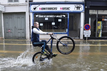 A man rides a bike through flooded streets of Montargis, south of Paris, on June 1, 2016. Torrential downpours have lashed parts of northern Europe in recent days, leaving four dead in Germany, breaching the banks of the Seine in Paris and flooding rural roads and villages.  AFP PHOTO / DOMINIQUE FAGET