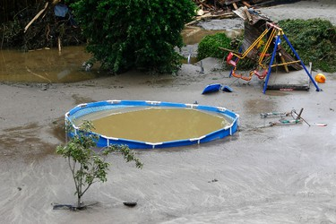 A playground and a pool is flooded by mud and water after the small town was hit by flooding in Simbach am Inn, Germany, Thursday, June 2, 2016. Several people have died. Several people have died in the flooding, which swept through the towns of Simbach am Inn and Triftern, while others have been reported missing. The waters have receded, and disaster relief crews were on the scene helping to clear the wreckage. There are warnings of more storms in the forecast. (AP Photo/Matthias Schrader)