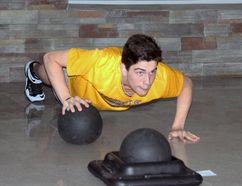 Damon Zapotichny, a Grade 10 Bishop Smith Catholic High School student, does Medicine Ball Push Ups at the St. Francis of Assisi School's boot camp. He is a former student of St. Francis.