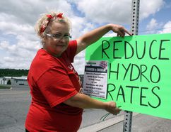 In this file photo, Sharon Chartrand posts a sign on Municipal Road 24 in Lively at a Hydro One - Enough is Enough event to protest high hydro prices. Ben Leeson/Postmedia Network