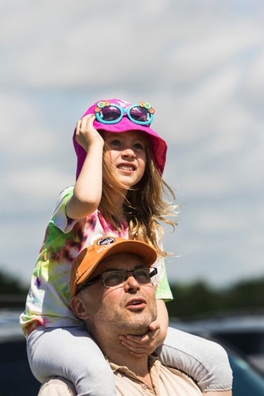 Juliet Voth checks out the 2016 Manitoba Air Show from the advantage of sitting on her dad's (Peter) shoulders. The air show took place in Portage-Southport, Man., on Saturday, June 4, 2016. (Brook Jones/Postmedia Network)