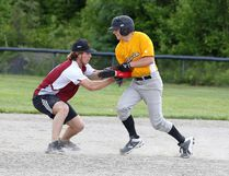 St. Charles Cardinals' Blake Purcell puts a tag on Notre Dame Alouettes' Cameron Mostoway during the boys city championship slo-pitch game at the Centennial baseball diamonds in the Valley on Tuesday.