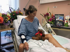 Maria Korcsmaros recovers from a shark attack in her hospital bed at Orange County Global Medical Center in Santa Ana, Calif., on Tuesday, June 7, 2016. The teddy bear next to her is wearing the swim goggles she used when she was bitten by a shark off the Orange County coast last month. (AP Photo/Amy Taxin)