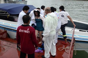 In this image made from video, a passenger is assisted from a police rescue boat at a pier in Phuket, Thailand, on June 8, 2016. Police say two speedboats carrying 62 tourists have collided off the coast of southern Thailand, leaving a number injured. (AP Photo)