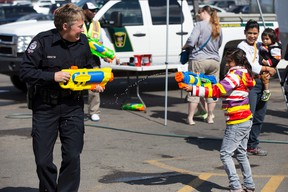 Noemi, 9, and EPS Cst. Amanda Trenchard, from West Division, play with squirt guns during Free The Fuzz at the South Edmonton Common Walmart in 2014. Free The Fuzz is a fundraiser for Special Olympics Alberta.