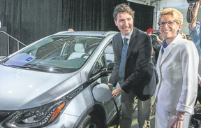Prime Minister Justin Trudeau, along with Ontario Premier Kathleen Wynne, plugs in a Chevrolet Bolt electric car in Oshawa on June 10, 2016. (Dave Thomas/Toronto Sun)