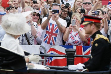 """People take pictures of Britain's Kate, Duchess of Cambridge, The Duchess of Cambridge and Prince Harry as they ride in a carriage during the Trooping The Colour parade at Buckingham Palace, in London, Saturday, June 11, 2016. Hundreds of soldiers in ceremonial dress have marched in London in the annual Trooping the Colour parade to mark the official birthday of Queen Elizabeth II. The Trooping the Colour tradition originates from preparations for battle, when flags were carried or """"trooped"""" down the rank for soldiers to see. (AP Photo/Tim Ireland)"""