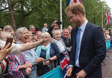 Britain's Prince Harry speaks to guests at the Patron's Lunch, a special street party outside Buckingham Palace in London on June 12, 2016, as part of the three day celebrations for Queen Elizabeth II's official 90th birthday. Up to 10,000 people are expected to attend the Patron's Lunch along with the monarch, her husband Prince Philip, Prince William and Prince Harry.  / AFP PHOTO / POOL / Arthur Edwards