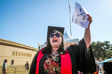 Stanford student Brianne Hunstman (C) encourages students to wear a 1/3 sign on their caps to show solidarity for a Stanford rape victim during graduation ceremonies at Stanford University, in Palo Alto, California, on June 12, 2016.   The 1/3 represents a statistic that claims one in three students will experience a sexual assault by the time they graduate college. Stanford students are protesting the university�s handling of rape cases alledging that the campus keeps secret the names of students found to be responsible for sexual assault and misconduct. / AFP PHOTO / GABRIELLE LURIE