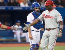 Philadelphia Phillies' Ryan Howard is congratulated by teammate Carlos Ruiz after hitting a solo home run as Toronto Blue Jays catcher Josh Thole looks on during seventh-inning action at the Rogers Centre in Toronto on June 13, 2016. (THE CANADIAN PRESS/Chris Young)