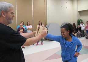 Don Robinet/Postmedia Network Henrie Timmers holds a board broken by Jiselle Hirnam on the final night of a free self defence course offered to women in Chatham.