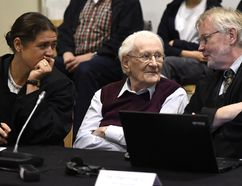 94-year-old former SS sergeant Oskar Groening sits between his lawyers Hans Holtermann, right, and Susanne Frangenberg, left, during the verdict of his trial Wednesday, July 15, 2015 at a court in Lueneburg, northern Germany. Groening, who served at the Auschwitz death camp was convicted on 300,000 counts of accessory to murder and given a four-year sentence. (Tobias Schwarz/Pool Photo via AP)