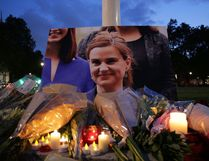 Floral tributes and candles are placed by a picture of slain Labour MP Jo Cox at a vigil in Parliament square in London on June 16, 2016. Cox died after a shock daylight street attack, throwing campaigning for the referendum on Britain's membership of the European Union into disarray just a week before the crucial vote. (DANIEL LEAL-OLIVAS/AFP/Getty Images)